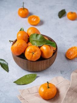 Süße und saftige mandarinen in einer holzschale auf einem blauen hintergrund. nahaufnahmebild