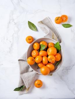 Süße und saftige mandarinen in einer keramikschale mit leinenserviette auf weißem marmorhintergrund. draufsicht und kopierraum