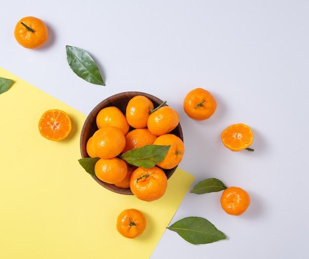 Süße und saftige mandarinen mit grünen blättern in einer holzschale auf einem trendigen gelbgrauen hintergrund. draufsicht und kopierraum