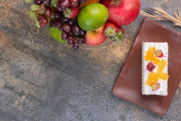 Süße verschiedene früchte auf glasteller mit stück kuchen auf dunklem teller