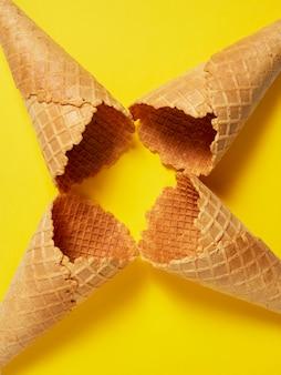 Süße waffeleis-eistüte auf gelbem hintergrund, sommer und leerem konzept. draufsicht. flach liegen
