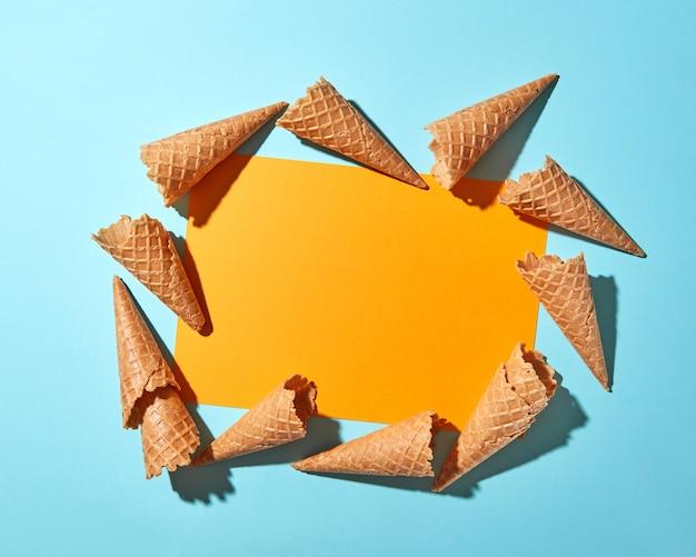 Süße waffelkegel zum nachtisch leer auf hellblauem papierhintergrund mit kopierraum. frühlings- oder sommeressenkonzept. ansicht von oben.
