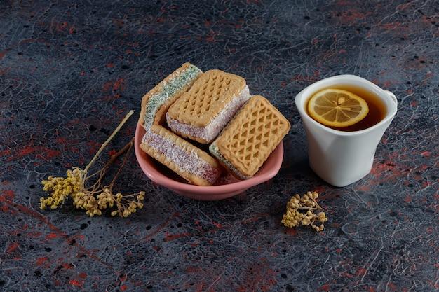 Süße waffeln mit einer weißen tasse heißen tees und einer mimosenblüte