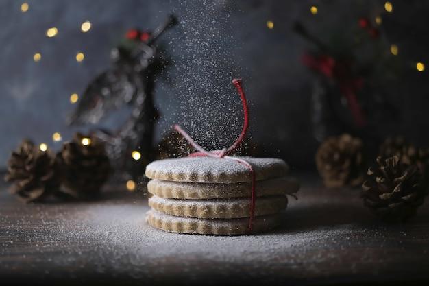 Süße weihnachtsplätzchen, die mit einem seil auf einem verschwommenen bokeh-hintergrund gebunden sind