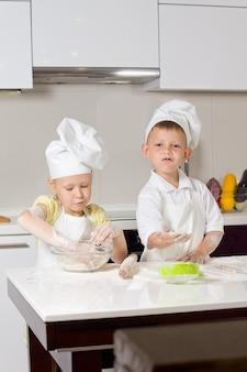 Süße weiße kleine köche backen auf weißem holztisch in der küche