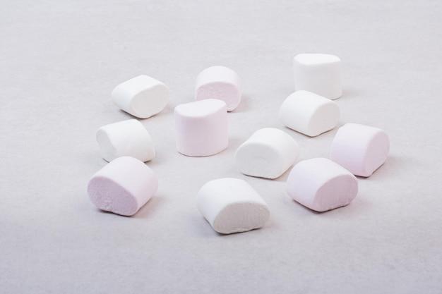 Süße weiße marshmallows auf weißem tisch. Kostenlose Fotos