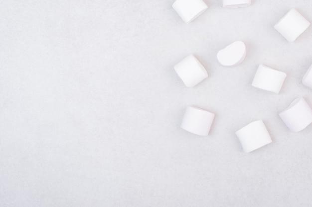 Süße weiße marshmallows auf weißem tisch.