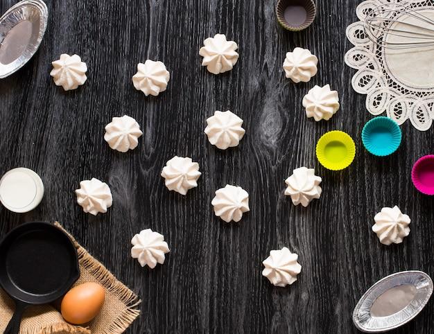 Süße weiße meringe und andere komponenten auf einem hölzernen hintergrund