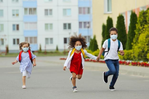 Süße weiße und schwarze schüler rennen zurück zur schule.