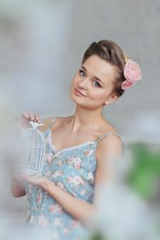 Süße zarte mädchenpyjamablumen der jungen frau und zopfhaar, welche die aufstellung in einem studio träumt