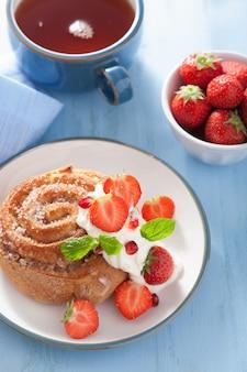 Süße zimtschnecke mit sahne und erdbeere zum frühstück