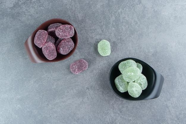 Süße zuckergelee-bonbons auf dunklen tellern