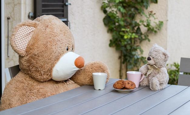 Süße zwei teddybären, die draußen am tisch mit tasse tee und keksen sitzen.