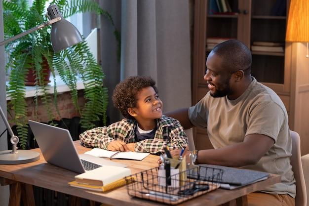 Süßer afrikanischer schüler und sein vater sitzen am tisch in der häuslichen umgebung und schauen sich lächelnd vor dem laptop-display an