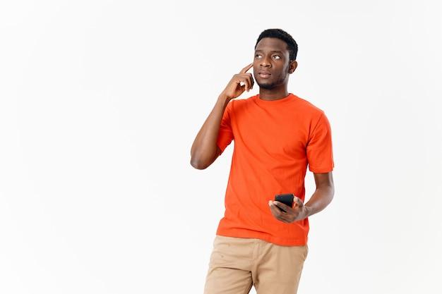 Süßer afroamerikaner in einem t-shirt und shorts mit einem handy
