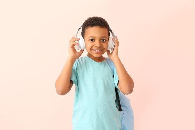 Süßer afroamerikanischer schuljunge mit kopfhörern
