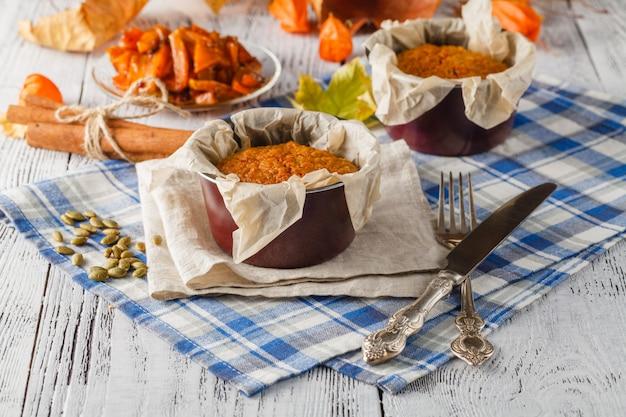 Süßer apfelkuchen serviert mit äpfeln und teetasse auf holzteller über tisch