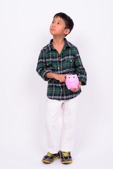 Süßer asiatischer junge, der grünes kariertes hemd gegen weiße wand trägt
