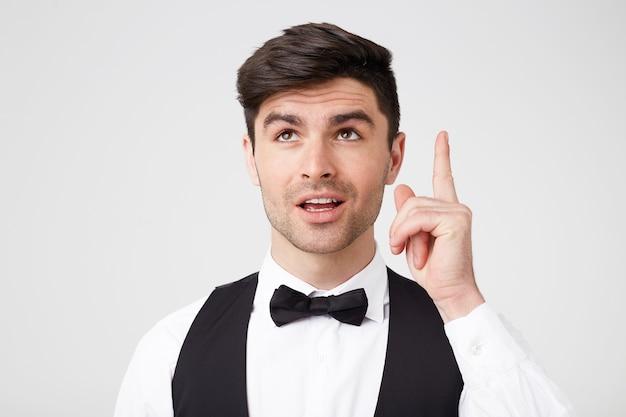 Süßer attraktiver gutaussehender mann mit fliege im anzug zeigt mit zeigefinger nach oben, wie es eine großartige idee hat