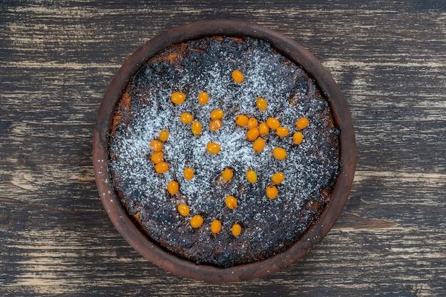 Süßer auflauf mit verbrannter kruste auf holztisch. keramikschale mit gebackenem hüttenkäse-auflauf, nahaufnahme, ansicht von oben