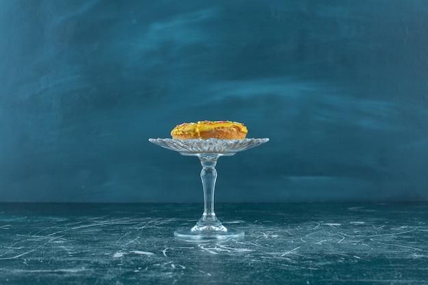 Süßer bagel mit schokoladenstückchen auf einem glassockel auf blauem hintergrund. foto in hoher qualität