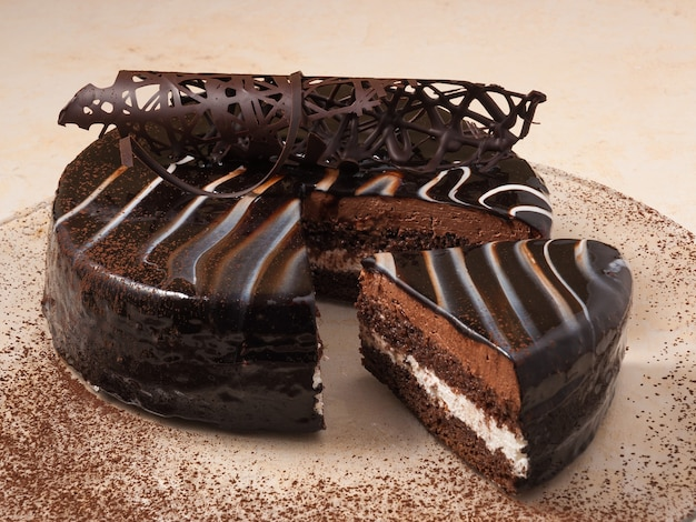 Süßer biskuitschokoladenkuchen auf einem teller, der mit kakaopulver verziert wird