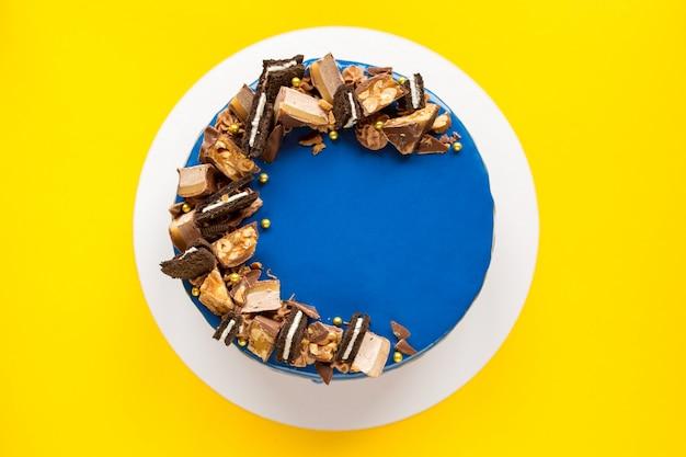 Süßer blauer kuchen am feiertag. süßes gebäck. geburtstag. glatter kuchen verziert mit schokoladen. gelber hintergrund