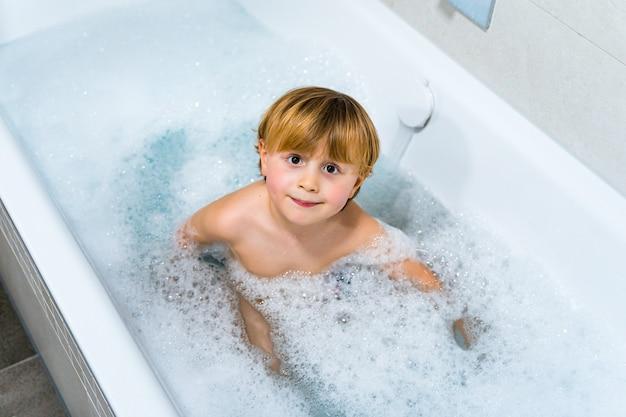 Süßer blonder kleinkindjunge, der bad in der badewanne nimmt und im seifenschaum spielt.