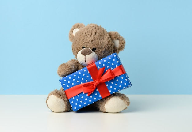 Süßer brauner teddybär, der eine schachtel in blauem papier und rotem seidenband auf weißem tisch hält. preis