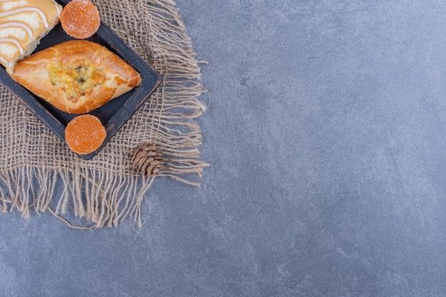 Süßer brötchenkuchen mit geleesüßigkeiten und tannenzapfen auf einem sack