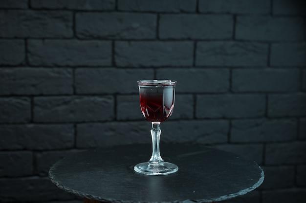 Süßer burgunderroter kirschlikör mit martini und tonic steht auf einem tisch auf einem schwarzen holztisch in einer bar. alkoholverkostung. cocktail in einem kristall vintage glas