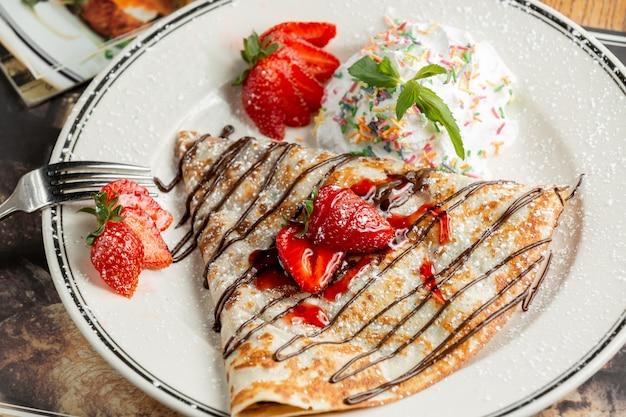 Süßer crêpe mit pulver und erdbeeren