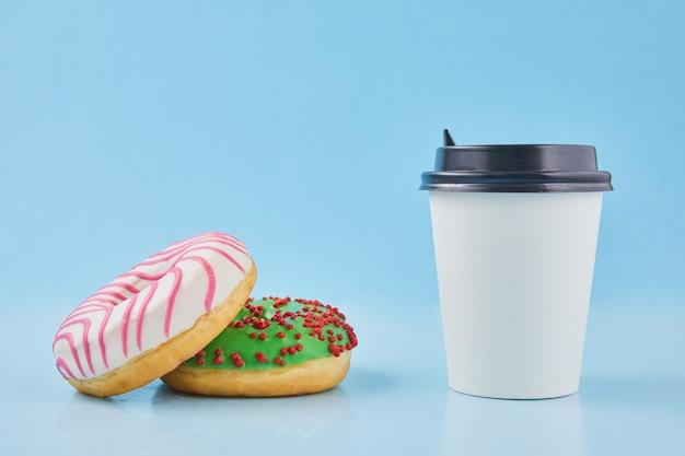 Süßer donut oder donut mit heißer tasse frisch gebrühtem kaffee oder tee pappbecher zum mitnehmen mit donuts