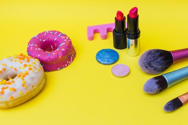 Süßer donut; zehenteiler; lippenstift; make-up pinsel und lidschatten auf gelbem hintergrund