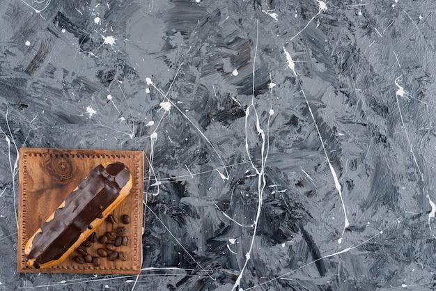 Süßer eclair mit schokoladenglasur auf marmorhintergrund gelegt.