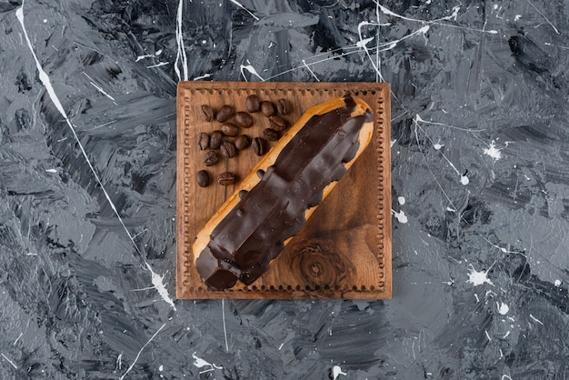 Süßer eclair mit schokoladenglasur auf marmoroberfläche.