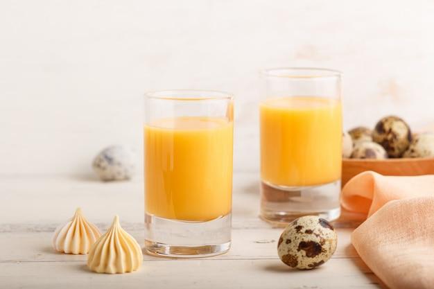 Süßer eierlikör im glas mit wachteleiern und meringen auf weißem hölzernem. seitenansicht, nahaufnahme.