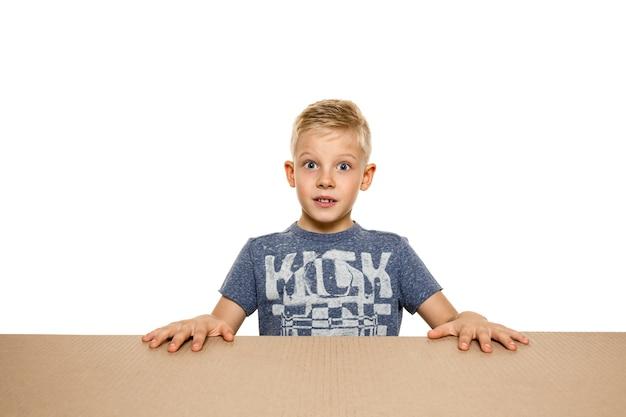 Süßer, erstaunter kleiner junge, der das größte postpaket öffnet