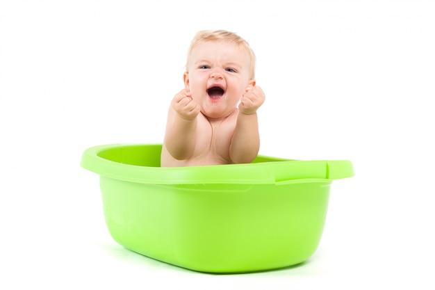Süßer fröhlicher kleiner junge in grüner wanne