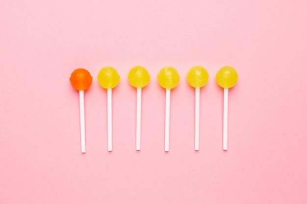 Süßer gelber und orange süßigkeitslutscher auf pastellrosa. minimalistische komposition.