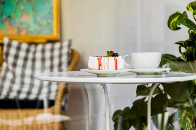 Süßer geschmackvoller käsekuchen mit beeren und kaffeetasse auf weißer schale in der kaffeestube