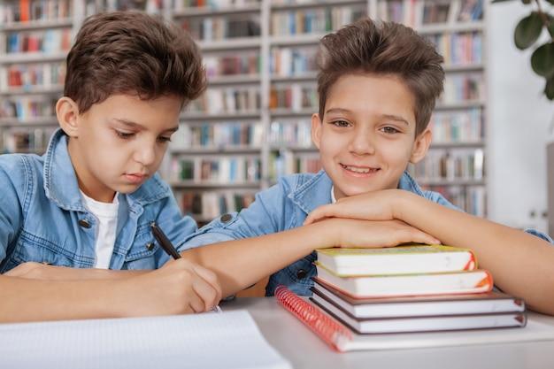 Süßer glücklicher kleiner junge, der lächelt, während sein zwillingsbruder hausaufgaben schreibt