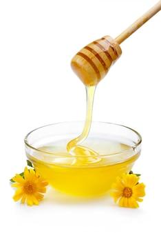 Süßer honig, der aus hölzernem schöpflöffel in der glasschüssel lokalisiert gießt