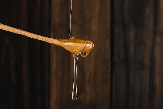 Süßer honig, der vom hölzernen löffel tropft