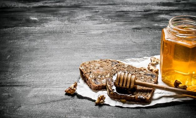 Süßer honig im glas und fruchtbrot mit walnüssen auf schwarzem rustikalem hintergrund