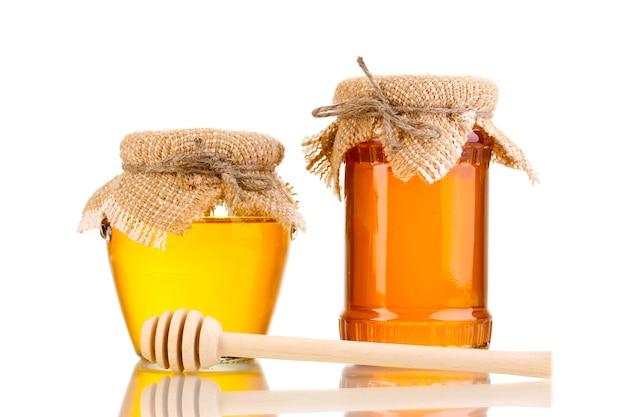 Süßer honig in gläsern mit nieselregen lokalisiert auf weiß