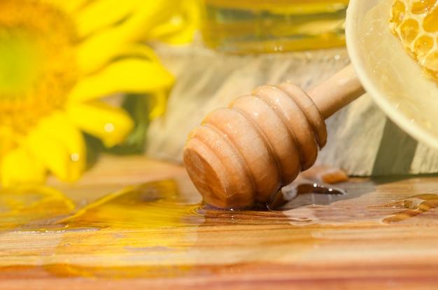 Süßer honig, stücke kämme und honigschöpflöffel auf unscharfem garten. honig tropft vom honigschöpflöffel