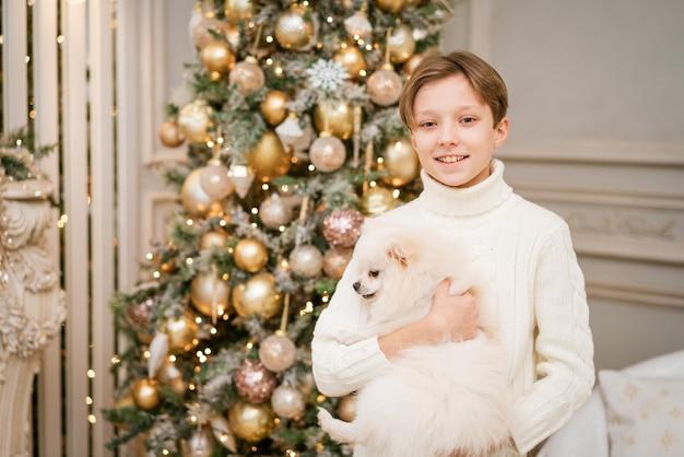 Süßer junge am weihnachtsbaum mit hund in erwartung der frohen weihnachten, glücklicher junge und hund umarmt ihr t...