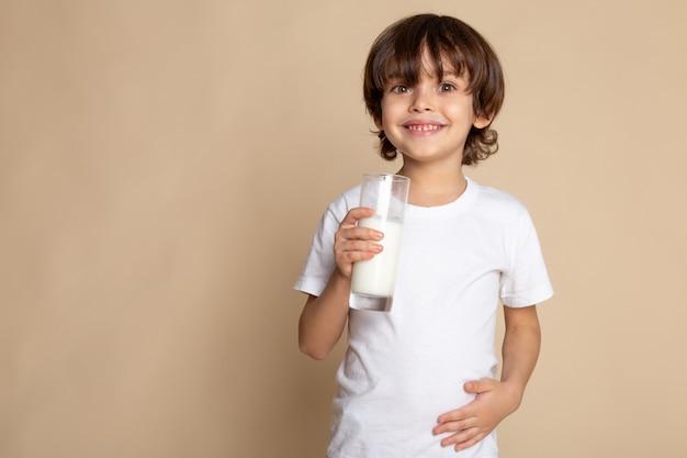 Süßer junge entzückend im weißen t-shirt, das weiße vollmilch auf rosa schreibtisch trinkt