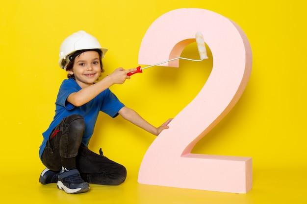 Süßer junge entzückender süßer im blauen t-shirt und in der dunklen hose nahe zahlenfigur auf gelber wand